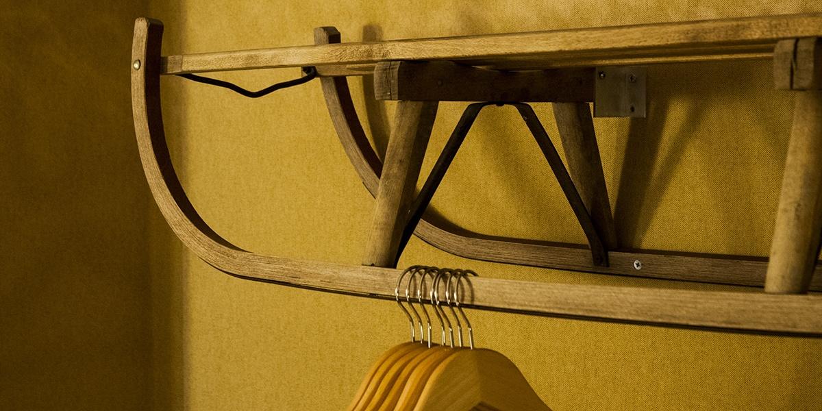 originele slee kapstok aan gele muur met hangertjes in de cosy suite van aplace / antwerp
