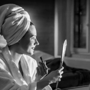 jonge dame die zich opmaakt in de cosy suite van aplace / antwerp