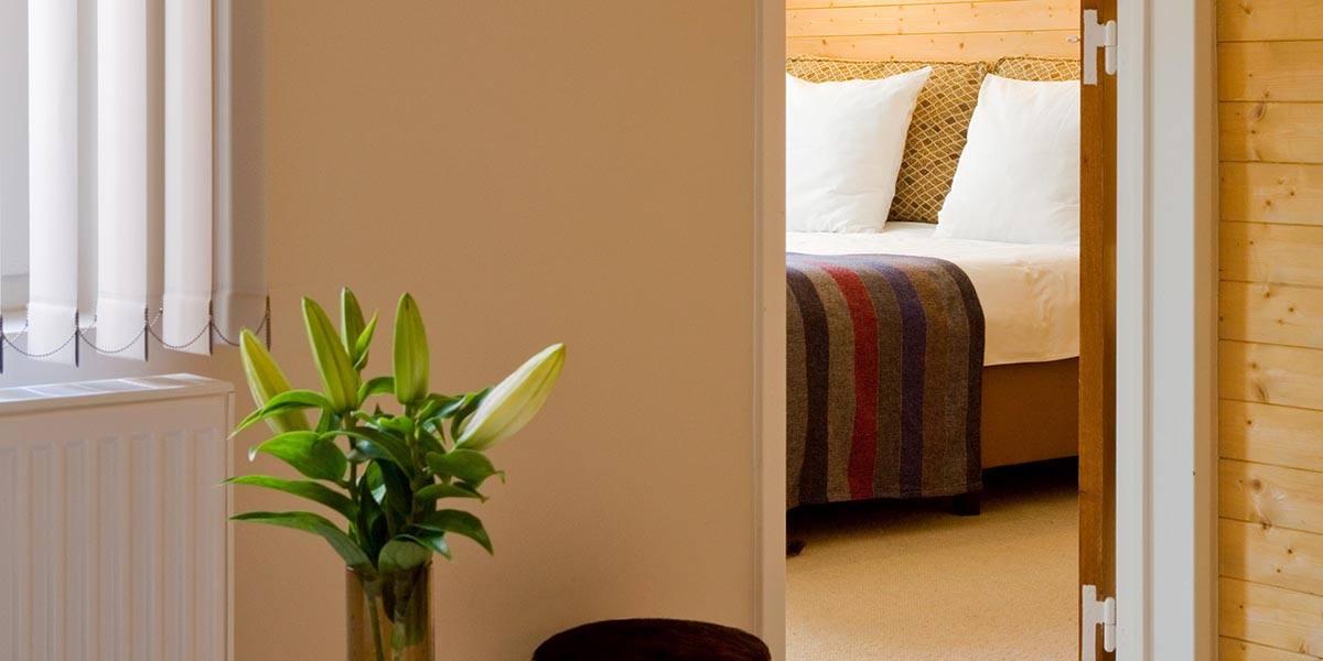 opgemaakt bed op de achtergrond met lelies op de voorgrond in de cosy suite van aplace / antwerp