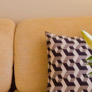 bank met sierkussen en bloemen in de cosy suite van aplace / antwerp