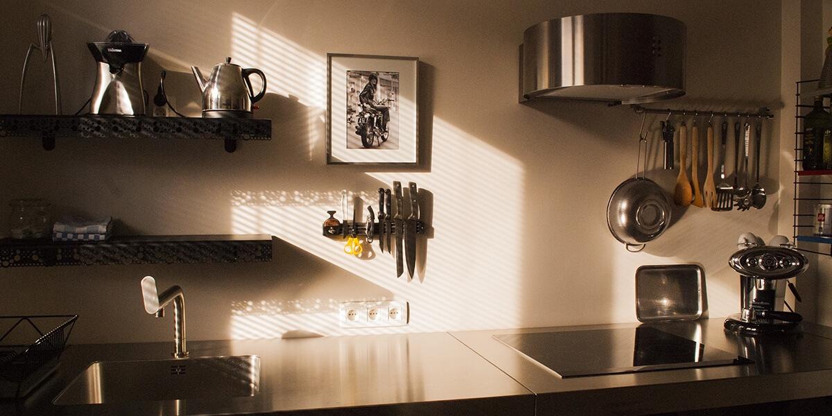 half open keuken van flat op de eerste verdieping van aplace antwerp ulthaup werktafel, een afwasmachine, een inductie kookplaat, koffiezetapparaat