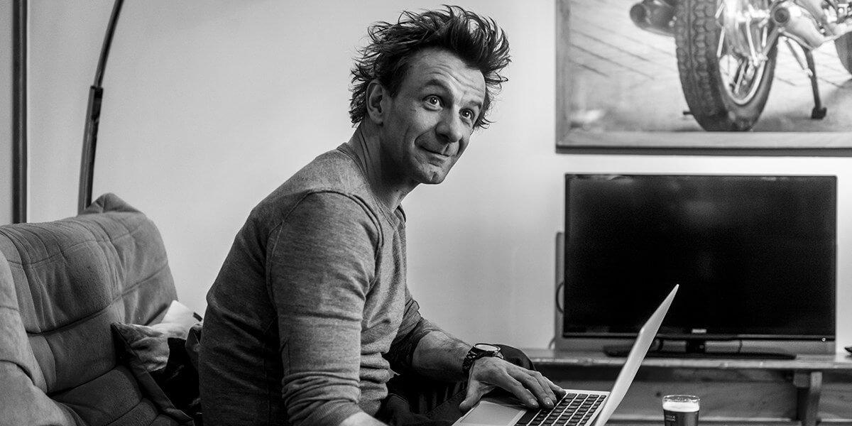 zwart wit foto van een man die zittend op de bank op zijn laptop aan het werken is in de flat op de eerste verdieping van aplace antwerp