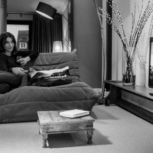 foto van een vrouw die zittend op een bank tv kijkt in de eerste verdieping flat van aplace antwerp ingericht in een warme bohemian chic stijl