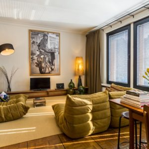 woonkamer ingericht in een warme – bohemian chic – stijl met banken, grote spiegel en lampen in de eerste verdieping flat van aplace antwerp