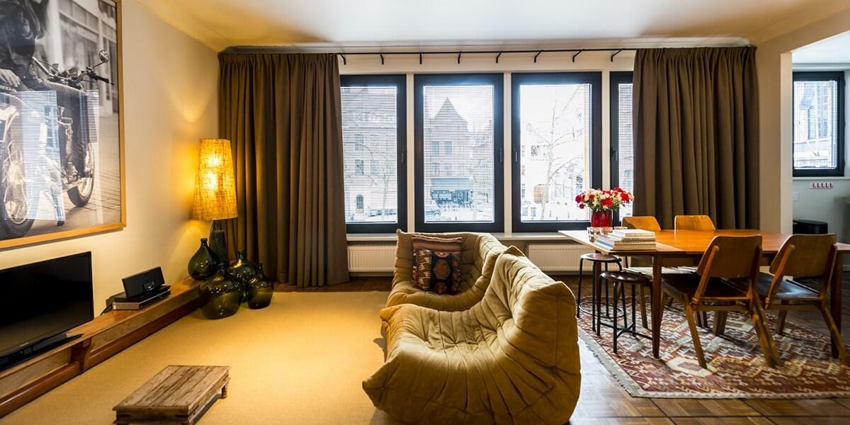 woonkamer ingericht in een warme – bohemian chic – stijl met bank, eetkamer en uitzicht op de vrijdagmarkt op de eerste verdieping flat van aplace antwerp
