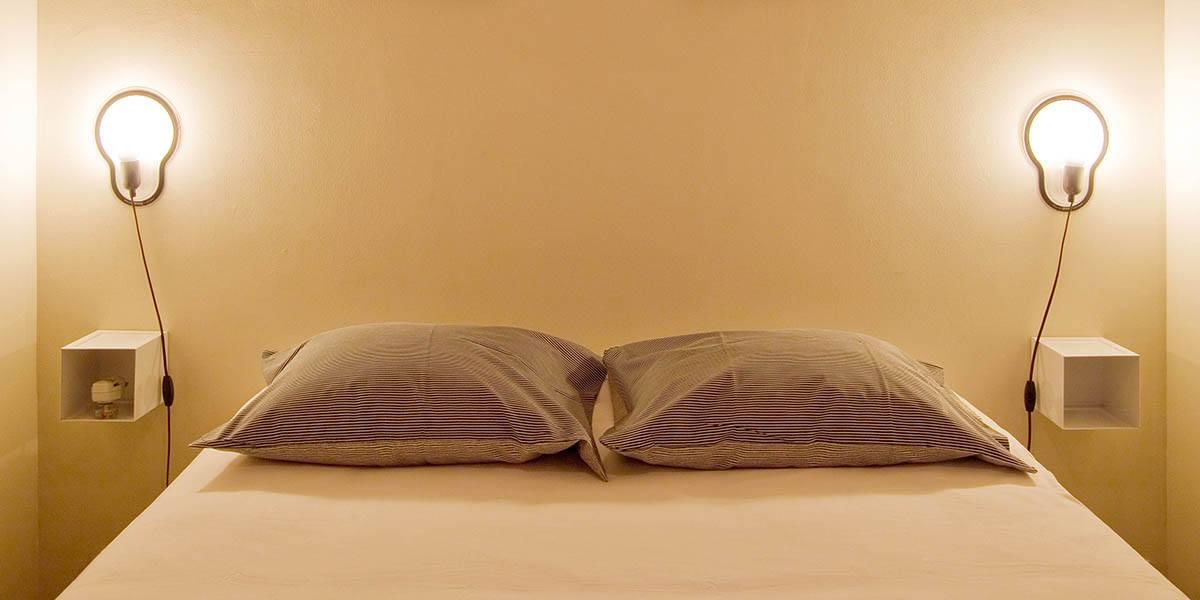 strak opgedekt bed met nachtkastjes en lampen op de eerste verdieping flat van aplace antwerp