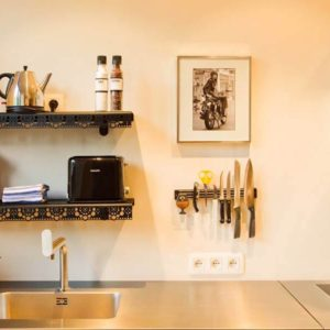 keuken met bulthaup aanrechtblad, gootsteen, waterkoker, cirtuspers, afdruiprek, keukenmessen, inductiekookplaat en afzuigkap