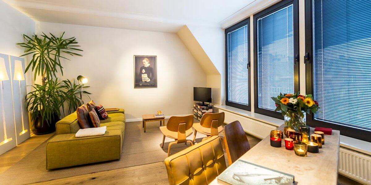 woonkamer in bohemien chic stijl met groene bank, retro stoeltjes in de flat op de derde verdieping van aplace