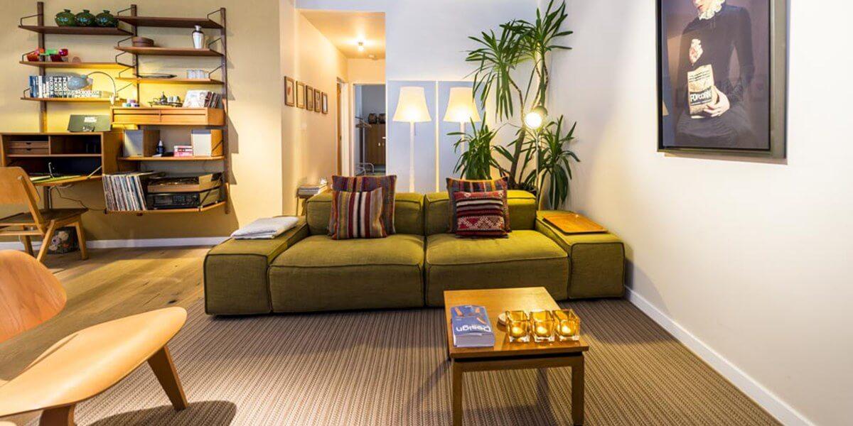 groene bank met sierkussens in woonkamer in bohemien chic stijl in de flat op de derde verdieping van aplace antwerp