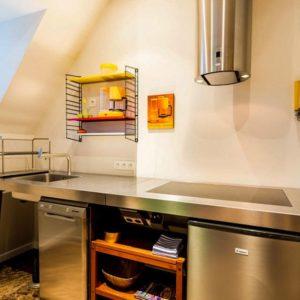 open keuken in de derde verdieping flat van aplace antwerp met Bulthaup werktafel een afwasmachine een inductie kookplaat oven afwasmachine