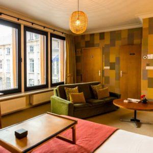 de retro ingerichte kamer van de square view suite van aplace antwerp met uitzicht op de Vrijdagsmarkt