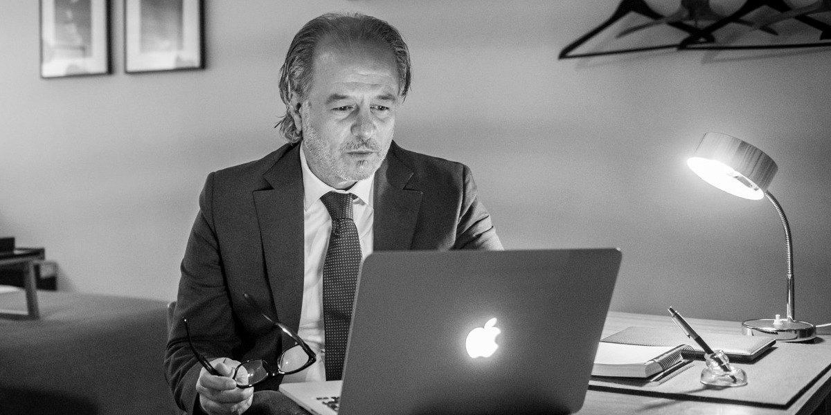 een zwart wit foto van een oudere man die op laptop aan het werken is aan het bureau in de square view suite van aplace antwerp