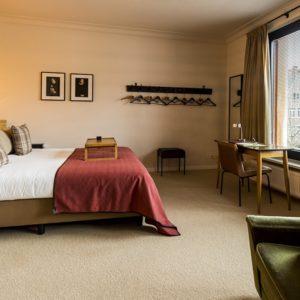 netjes opgemaakt bed met kussens in de square view suite van aplace / antwerp dat uitkijkt op de gebouwen van de vrijdagsmarkt