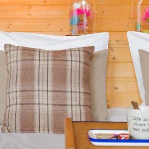 bed in de square view suite van aplace antwerp met sierkussens en koffiekopje op schotel en trollen met roze en blauw haar
