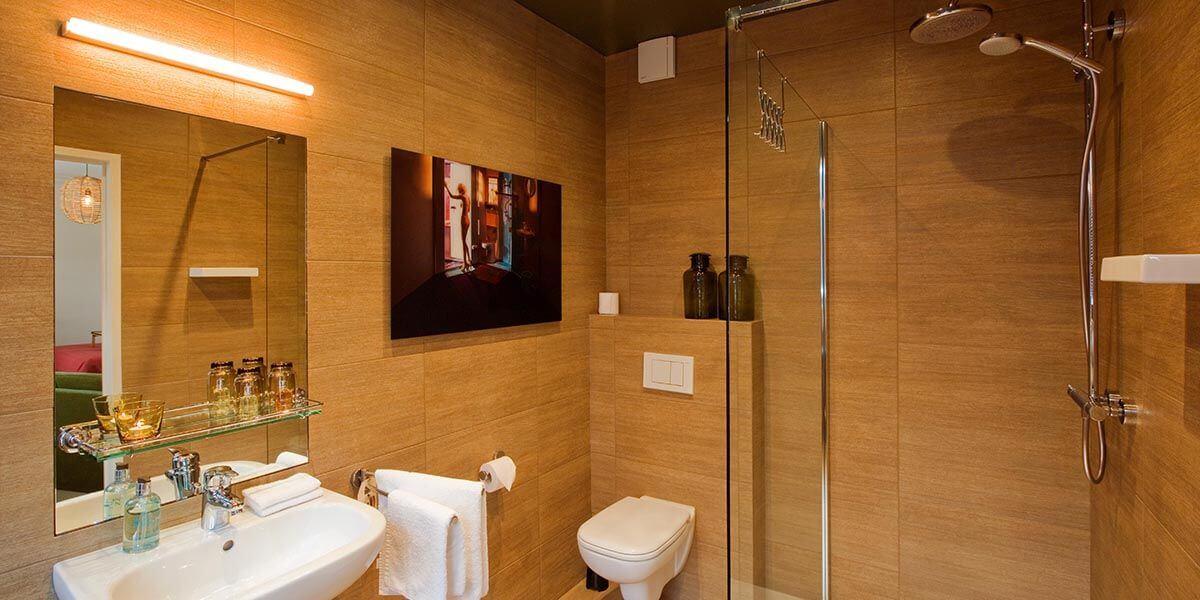 badkamer met regendouche, toilet, gootsteen en kunstfoto in de square view suite van aplace antwerp