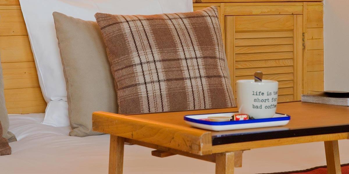 sierkussens op opgemaakt bed in de square view suite van aplace antwerp met koffiekopje en schotel op bedtafeltje