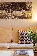zetel met sierkussen en zwart wit foto van fontein in de suite van aplace antwerp