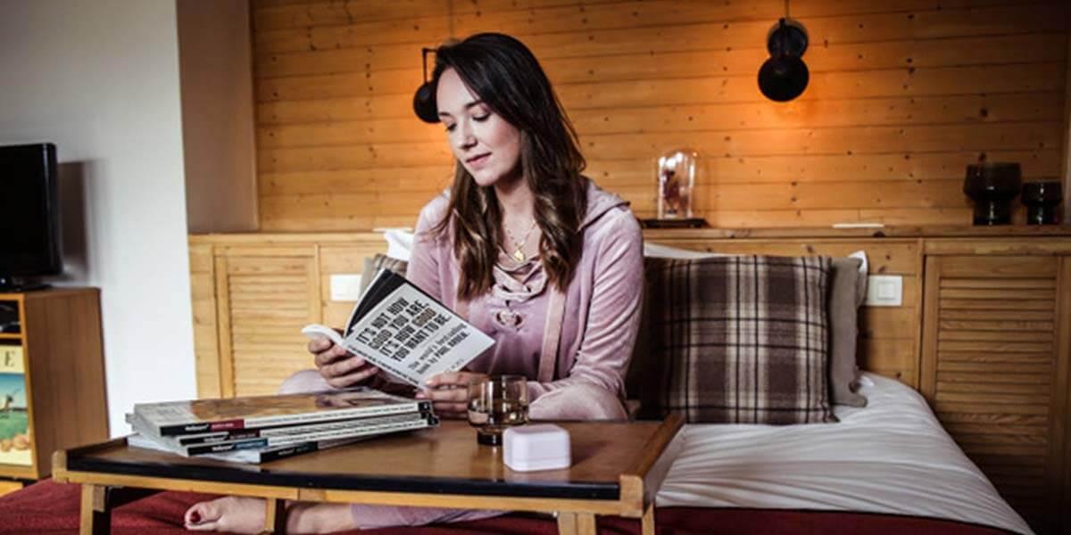 jonge vrouw leest boek in bed van de square view suite van aplace antwerp